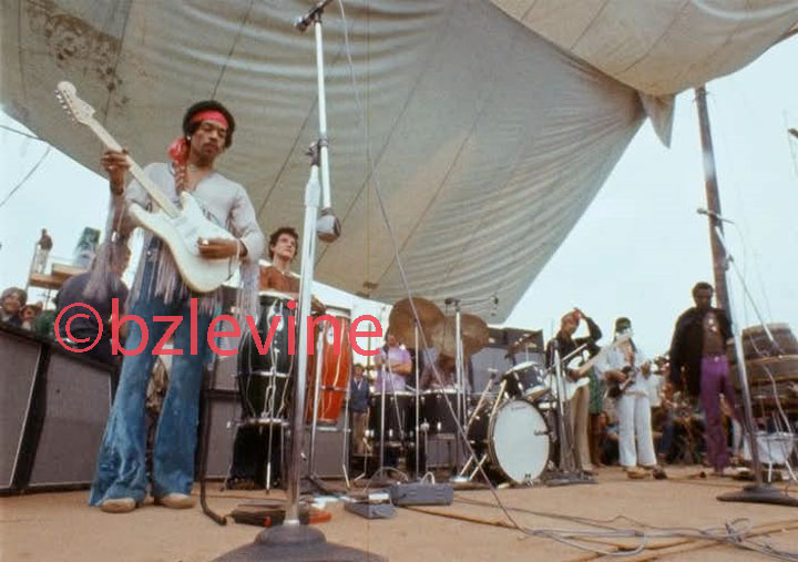 Jimi Hendrix Band of Gypsies performing monday morning at Woodstock as featured (p26-27) in the Jimi Hendrix Live at Woodstock Alblum's 12x12 36 page Promotional book commemorating the 35Th Anniversary of Jimi's performance at the Woodstock Festival